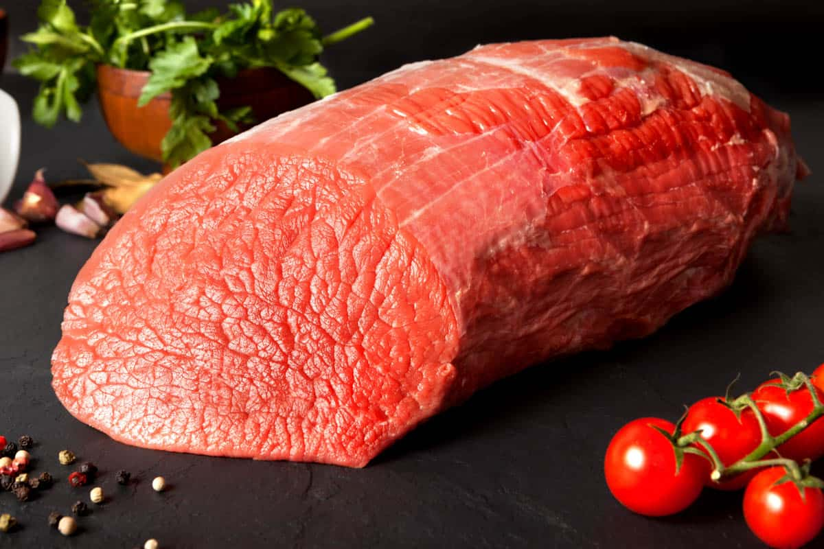 Eye of round beef on dark cutting board