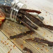 Jerky in jar with red pepper flakes on wood