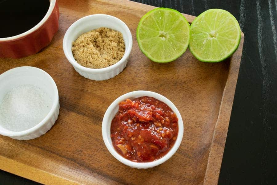 Chili lime jerky ingredients, lime, chili garlic, brown sugar on cutting board