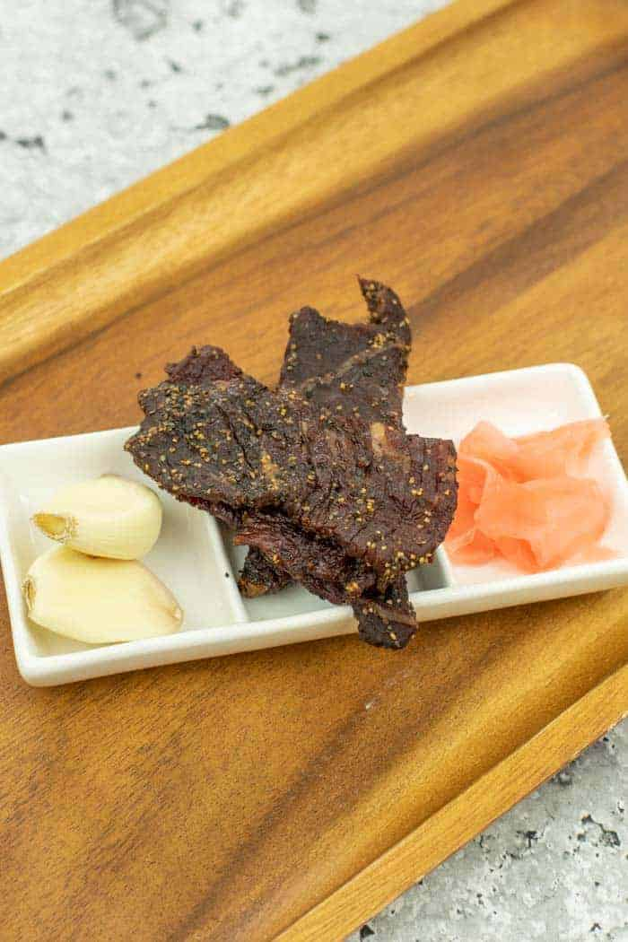 Teriyaki Beef jerky on dish with ginger and garlic backed by wood cutting board