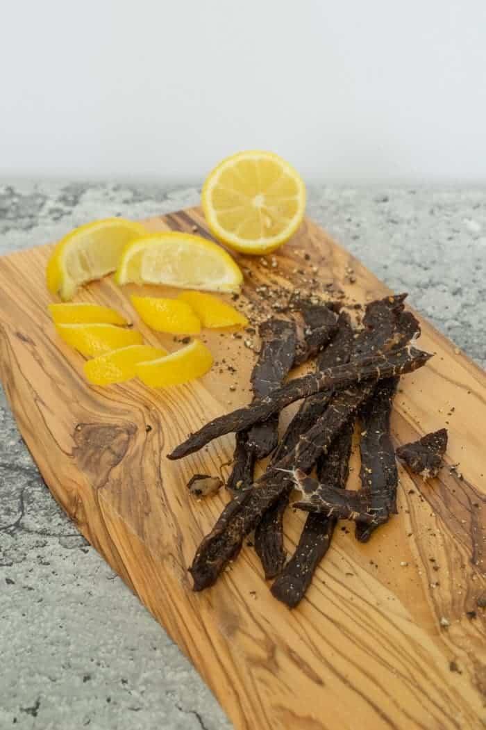 Lemon Pepper Beef jerky on cutting board with lemons
