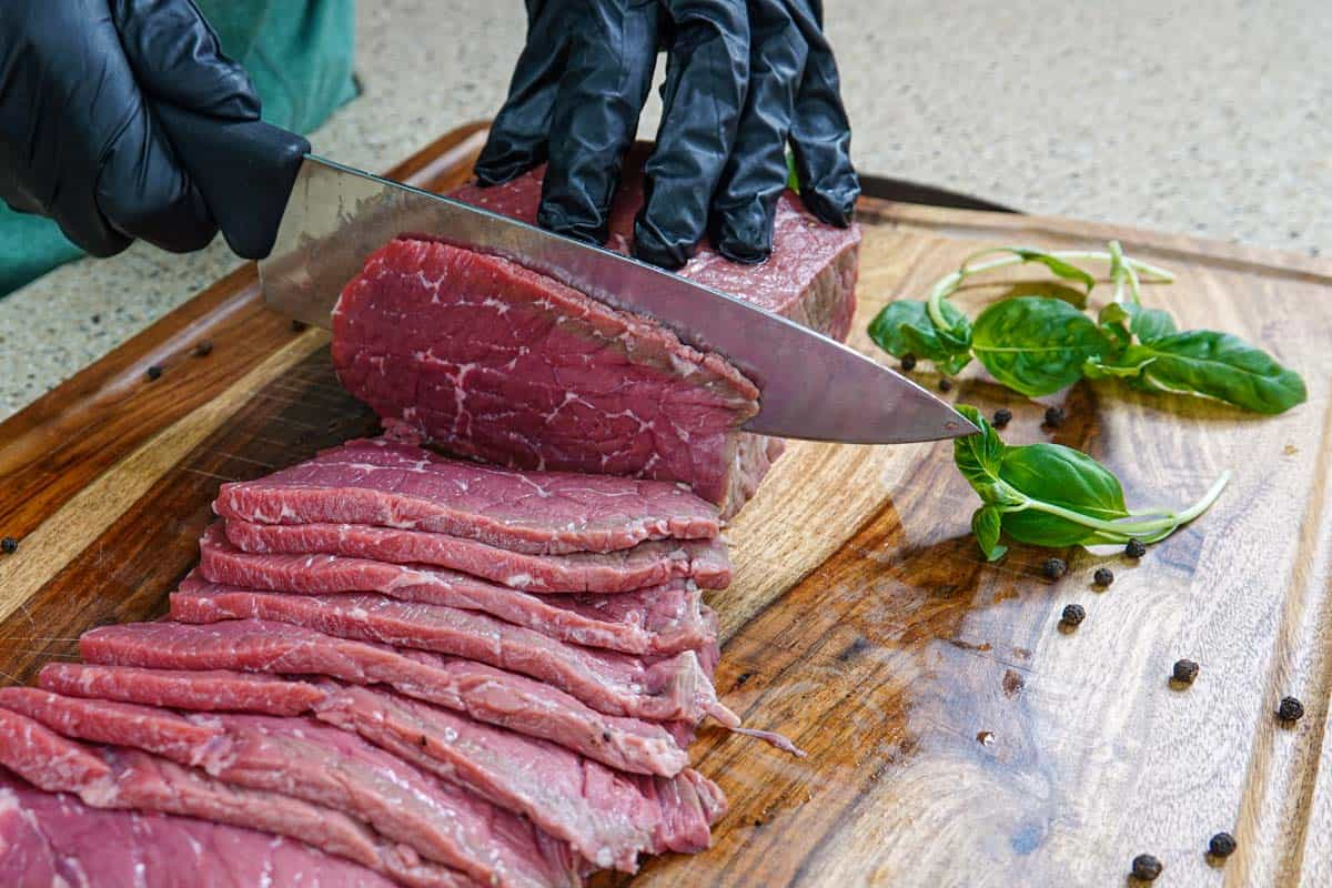 Slicing meat for beef jerky on cutting board with knife