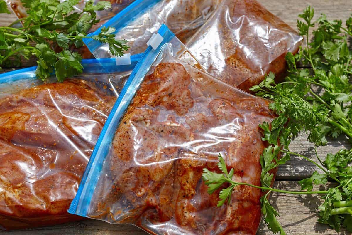 Jerky marinating in ziplock bags with cilantro decoration
