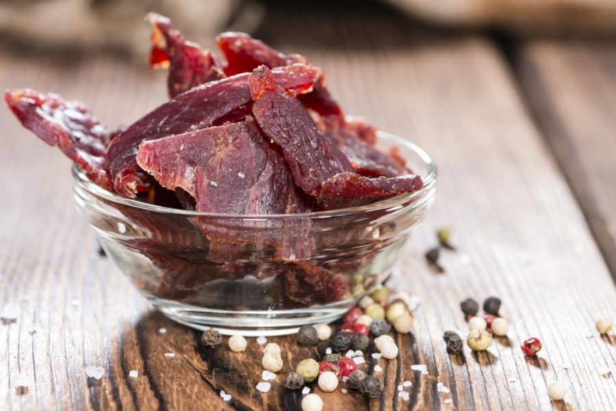 Smoked beef jerky in bowl with seasonings at base