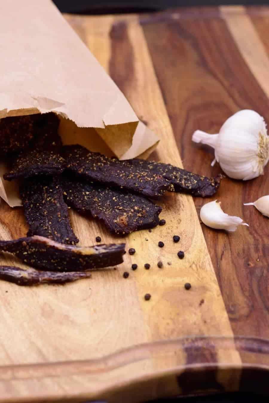 Garlic black pepper beef jerky on cutting board with black peppercorns and garlic