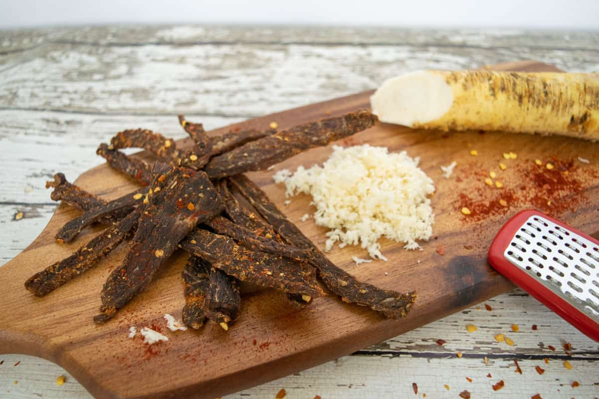 Beef jerky on cutting board with grated horseradish