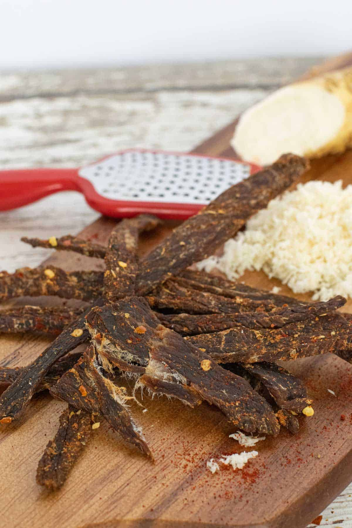 Cajun beef jerky on cutting board with horseradish and grater