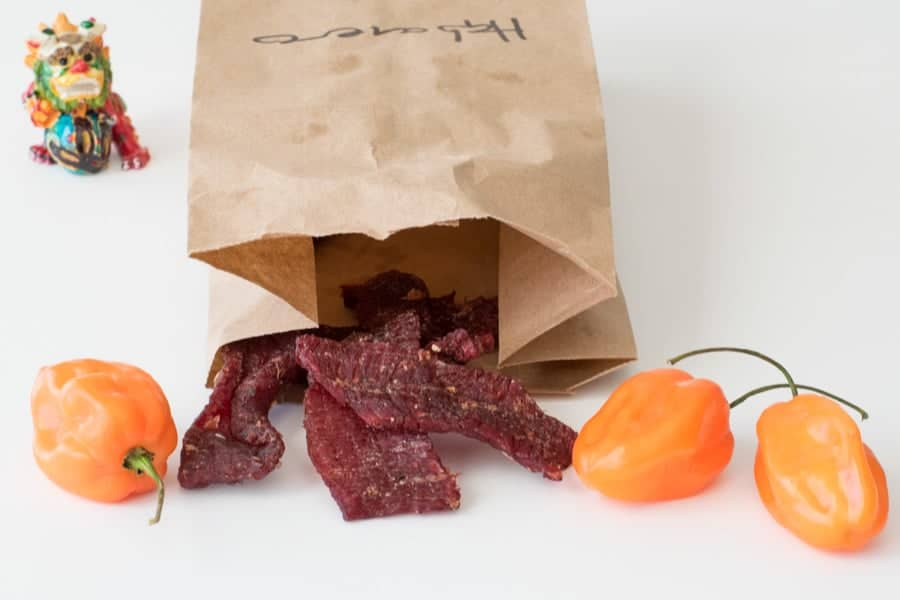 Beef jerky in brown bag with three habanero peppers