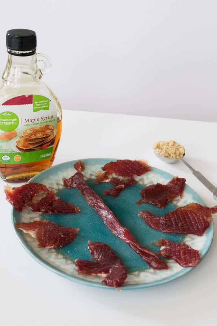 Sweet Maple Pork Jerky arranged on plate with bottle of maple syrup and tbsp of brown sugar
