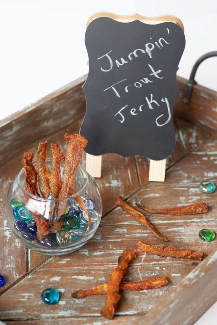 Fish jerky in a glass bowl with a sign that says jumping trout jerky