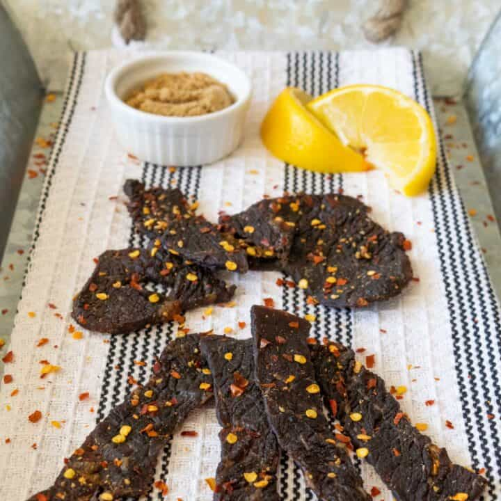 beef jerky on tray with lemons and spices