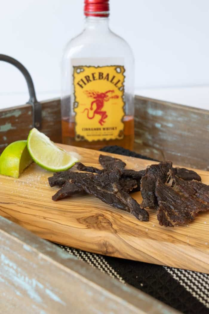 Beef jerky on cutting board with lime wedges and a bottle of Fireball whisky