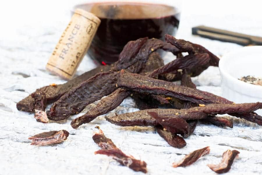 Corkscrew deer jerky with cork and wine close up
