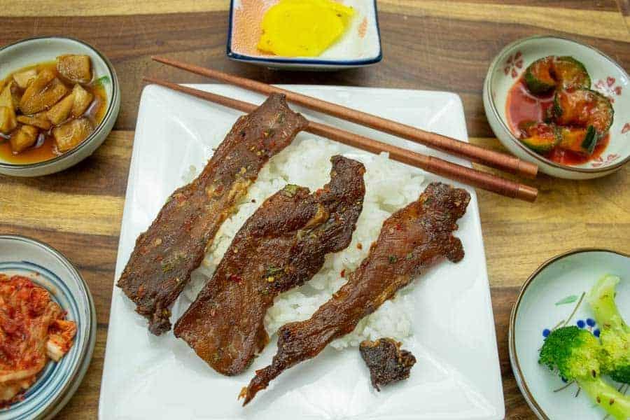 Pork jerky atop rice with korean small plates around