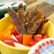 Italian Pork Jerky in dish with peppers and onions