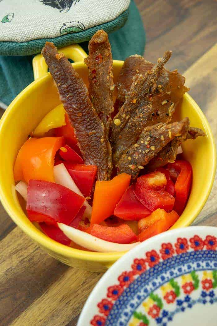 Italian pork jerky in yellow dish with pepper and onions