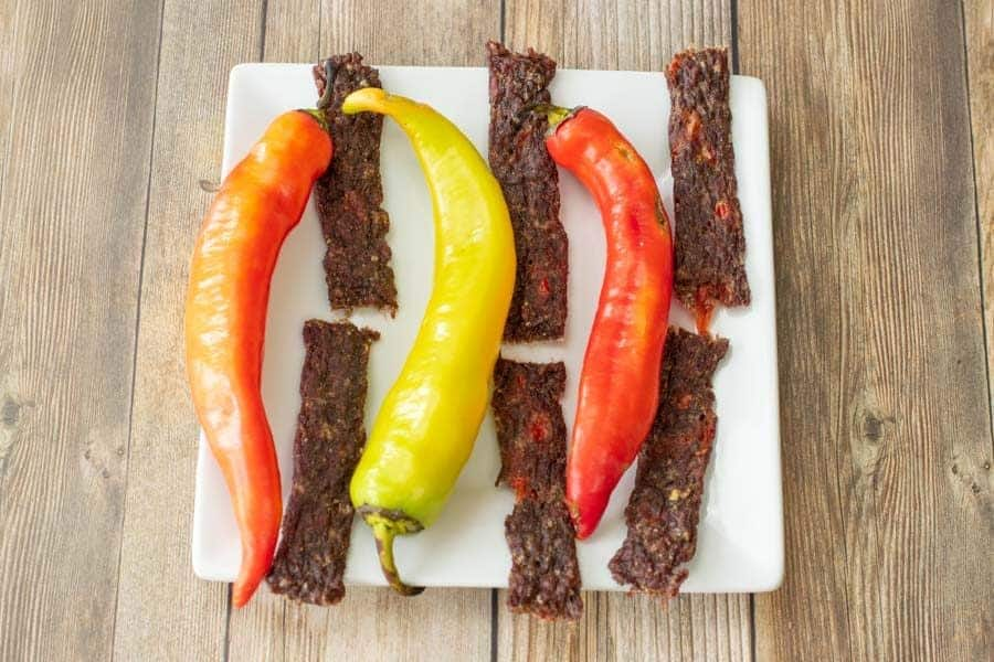 Wicked Fiery ground beef jerky on plate with banana peppers on wood background