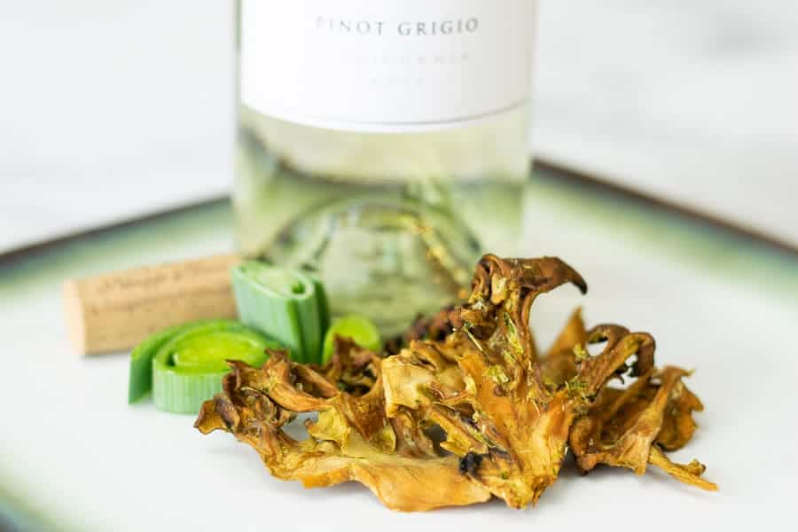 maitake mushroom jerky on plate with white wine bottle and cork