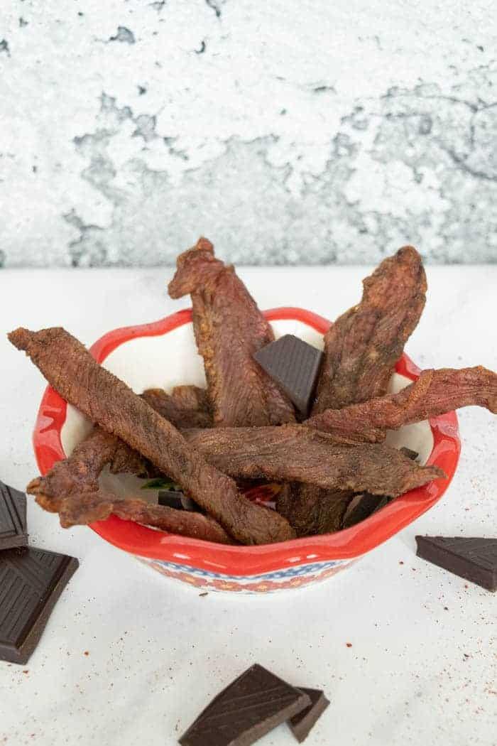 Mole turkey jerky in bowl with chocolate