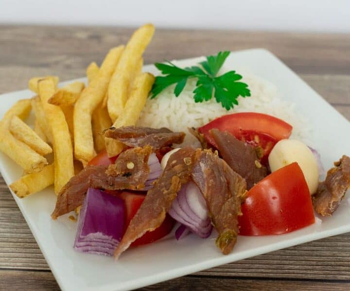 Peruvian jerky on plate with tomatoes, rice and french fries