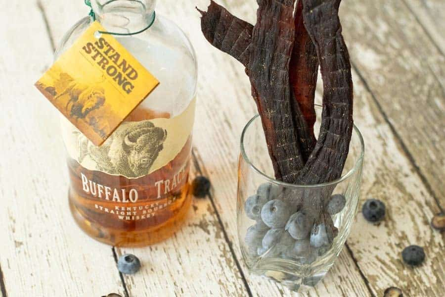 Deer jerky in glass next to bottle of bourbon bottle on wood table