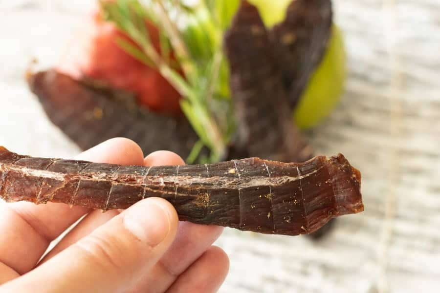 Deer jerky bending showing white fibers with pear in background