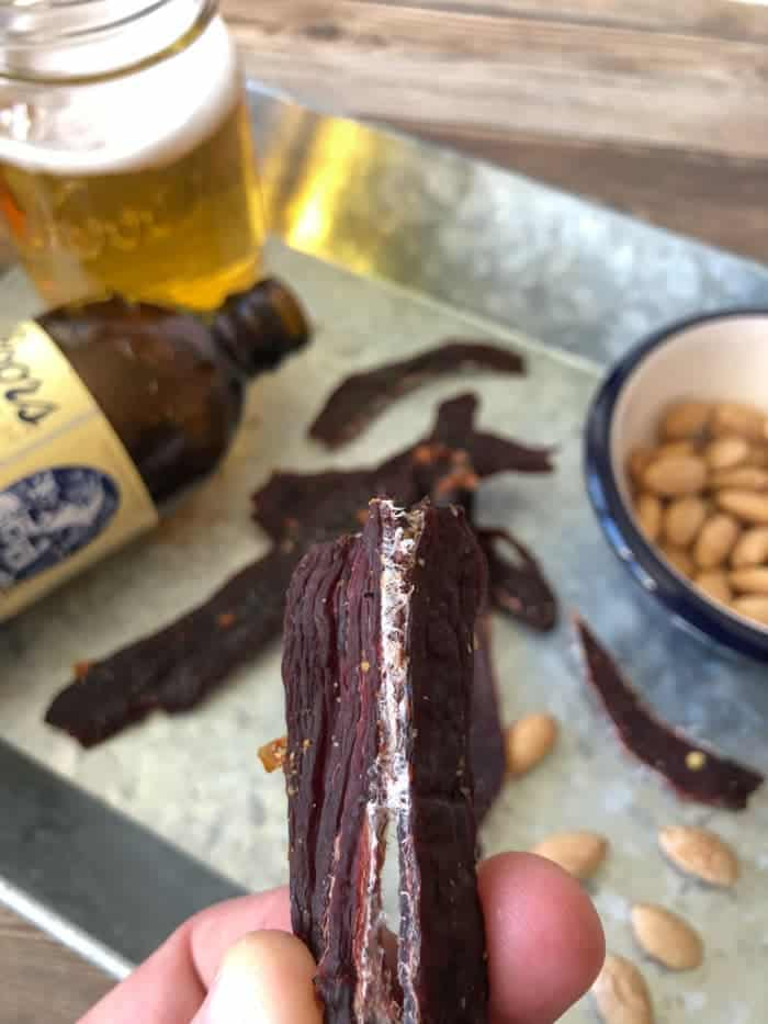 Deer jerky bent in half with beer and peanuts in dish in background