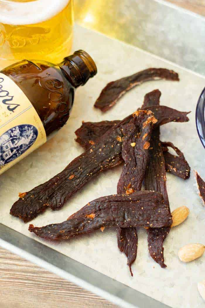 Deer jerky on platter with glass of beer and a coors original beer bottle
