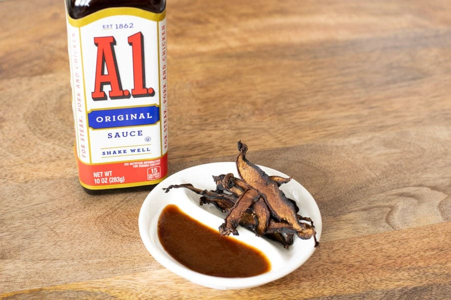 A1 sauce bottle and mushroom jerky on white plate on table