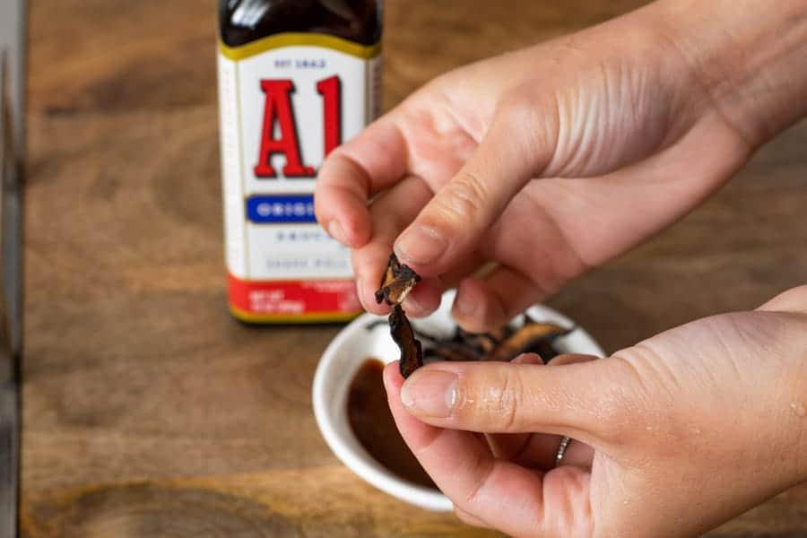 breaking a piece of mushroom jerky, A1 bottle on table