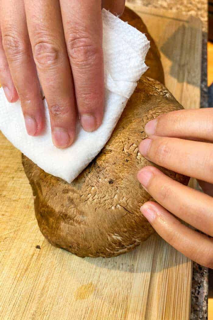 Hand wiping dirt from Portobello mushroom with wet paper towel