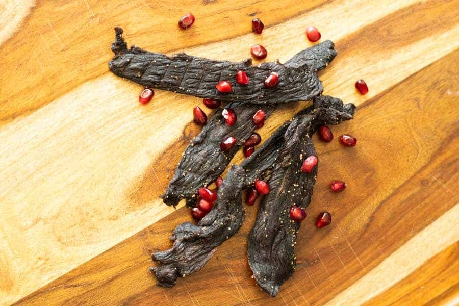 Pomegranate Deer Jerky on cutting board with pomegranates