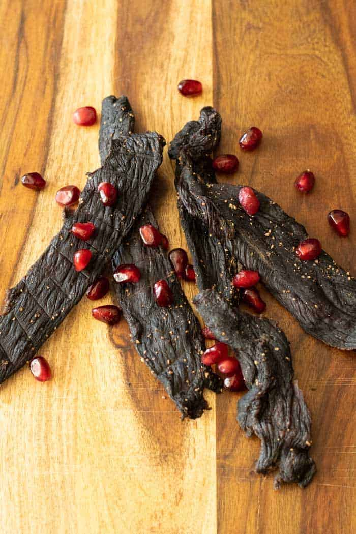 Pomegranate deer jerky on cutting board