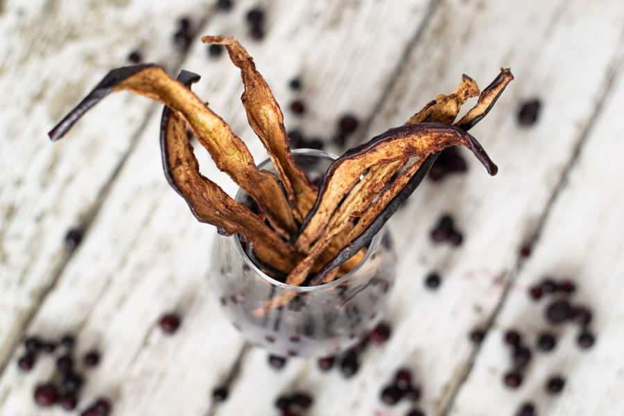 Eggplant jerky in glass with blueberries on white table