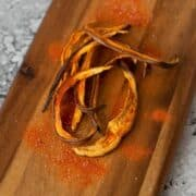 Eggplant Jerky on wooden cutting board with tomato powder
