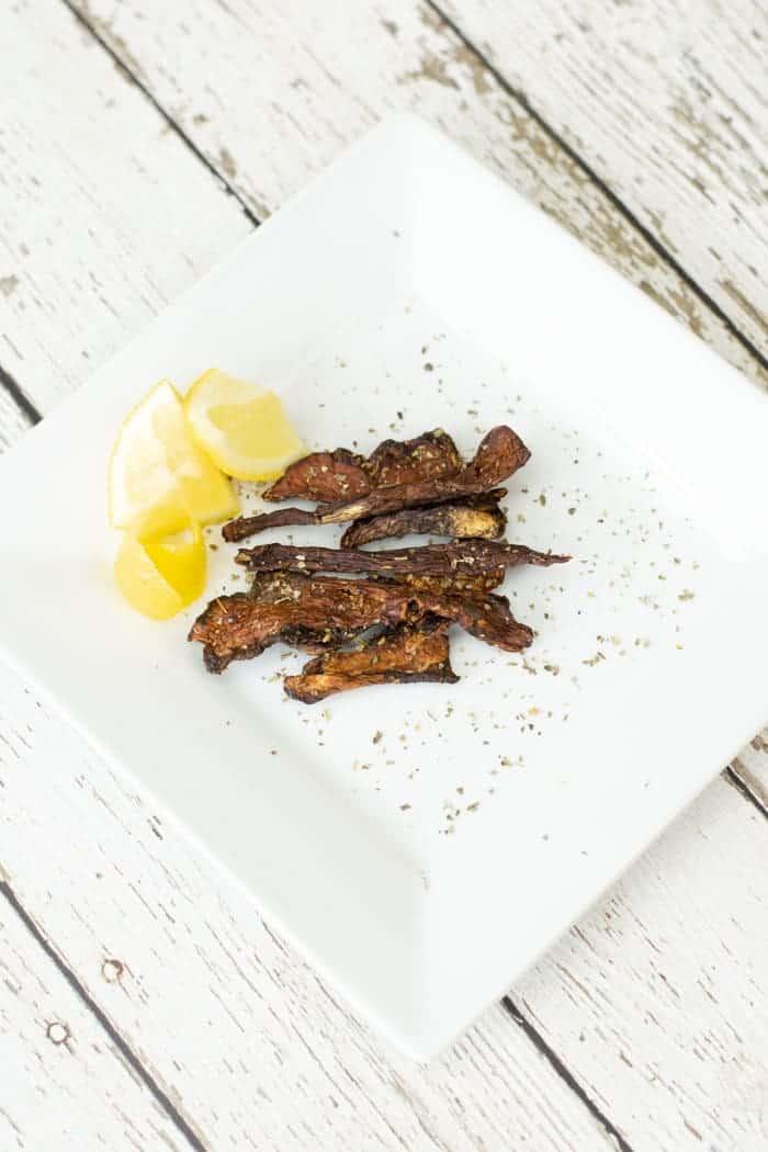 sliced lemons and porcini mushroom jerky on white plate