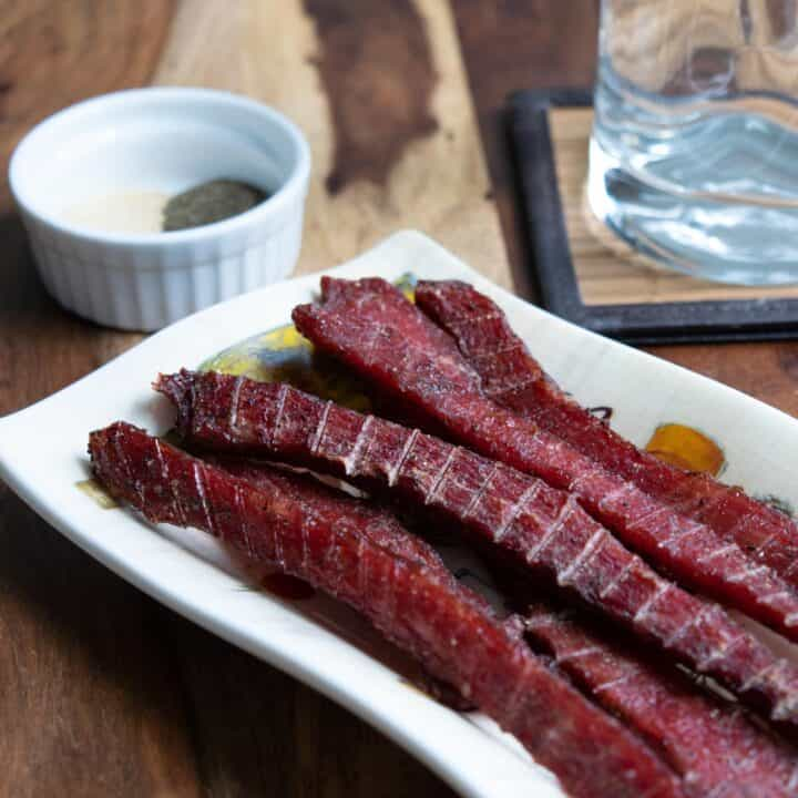 Beef jerky on plate with spices and glass of water