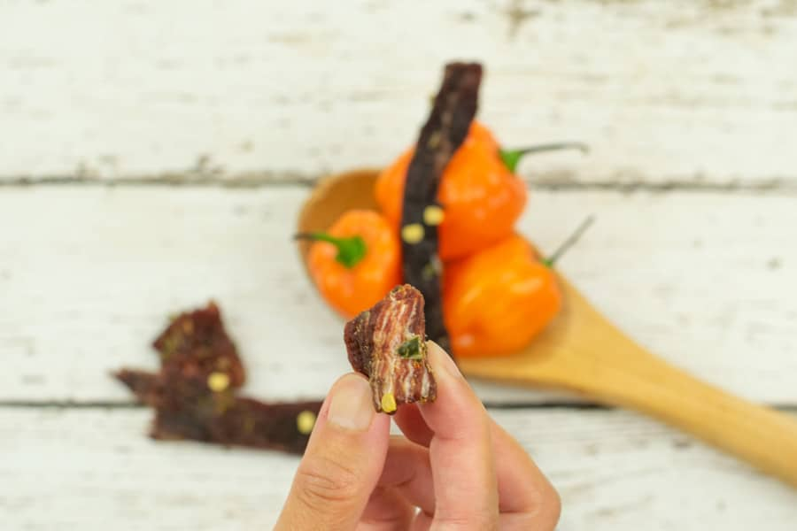 Testing jerky by bending with wood spoon holding habaneros