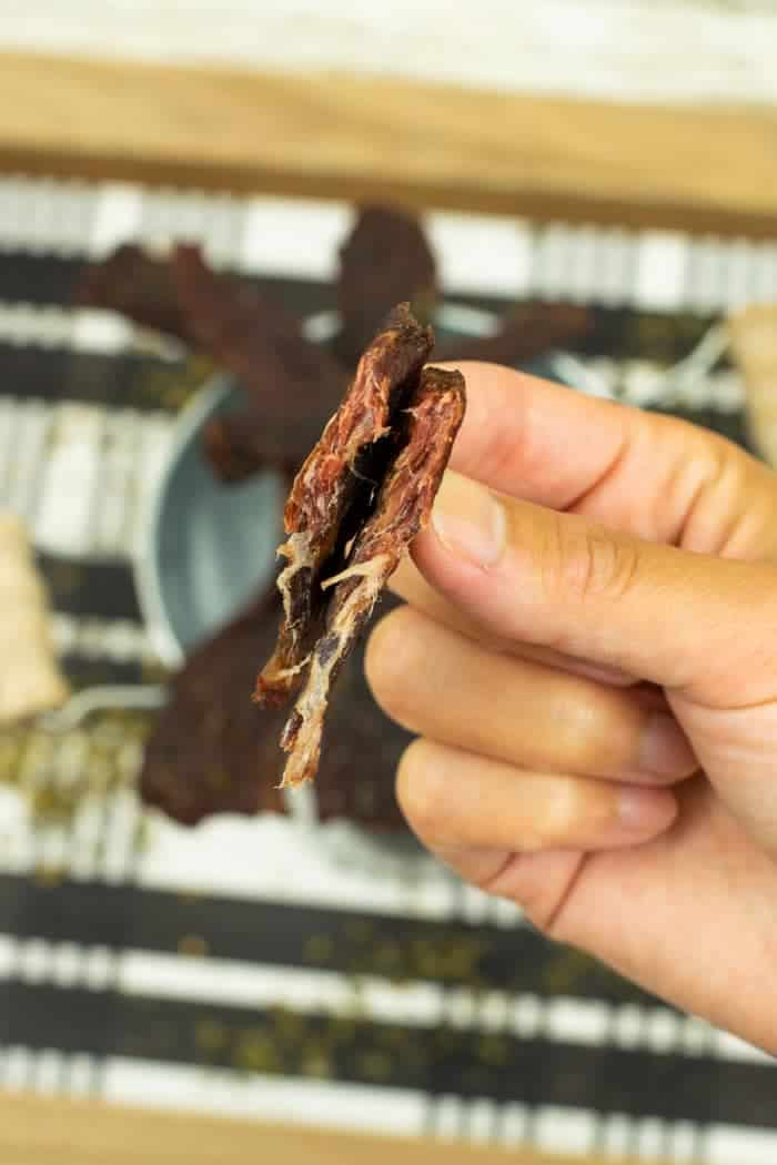 jerky bent showing it's finished drying held by hand