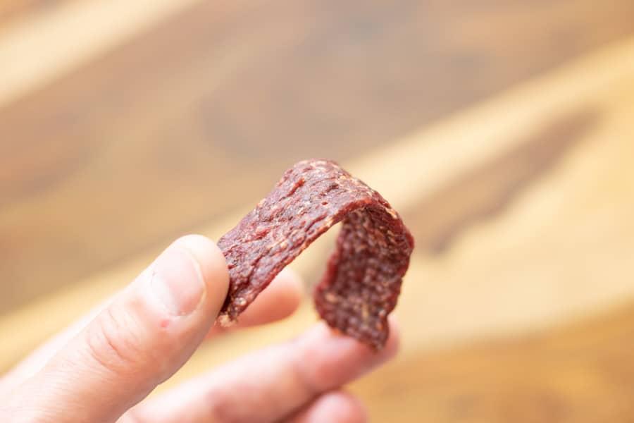ground beef jerky strip being bent in half