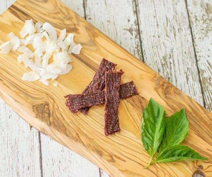 coconut ground beef jerky on cutting board with coconut shavings and basil