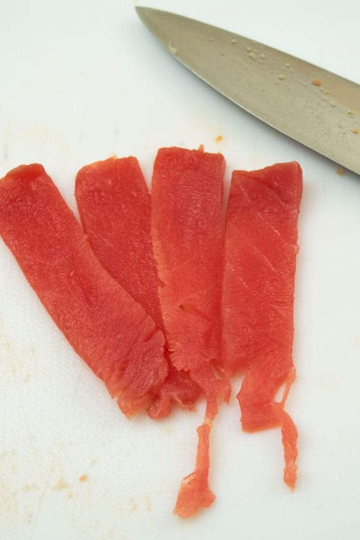 Tuna steak sliced for jerky with knife