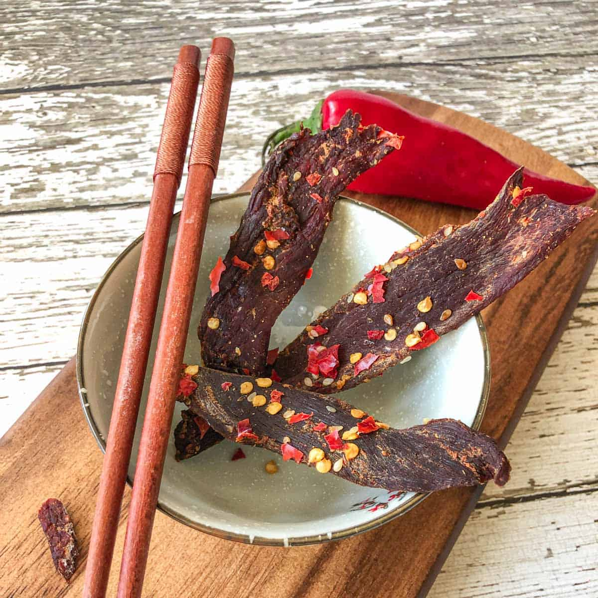 Venison jerky in bowl with chop sticks on cutting board