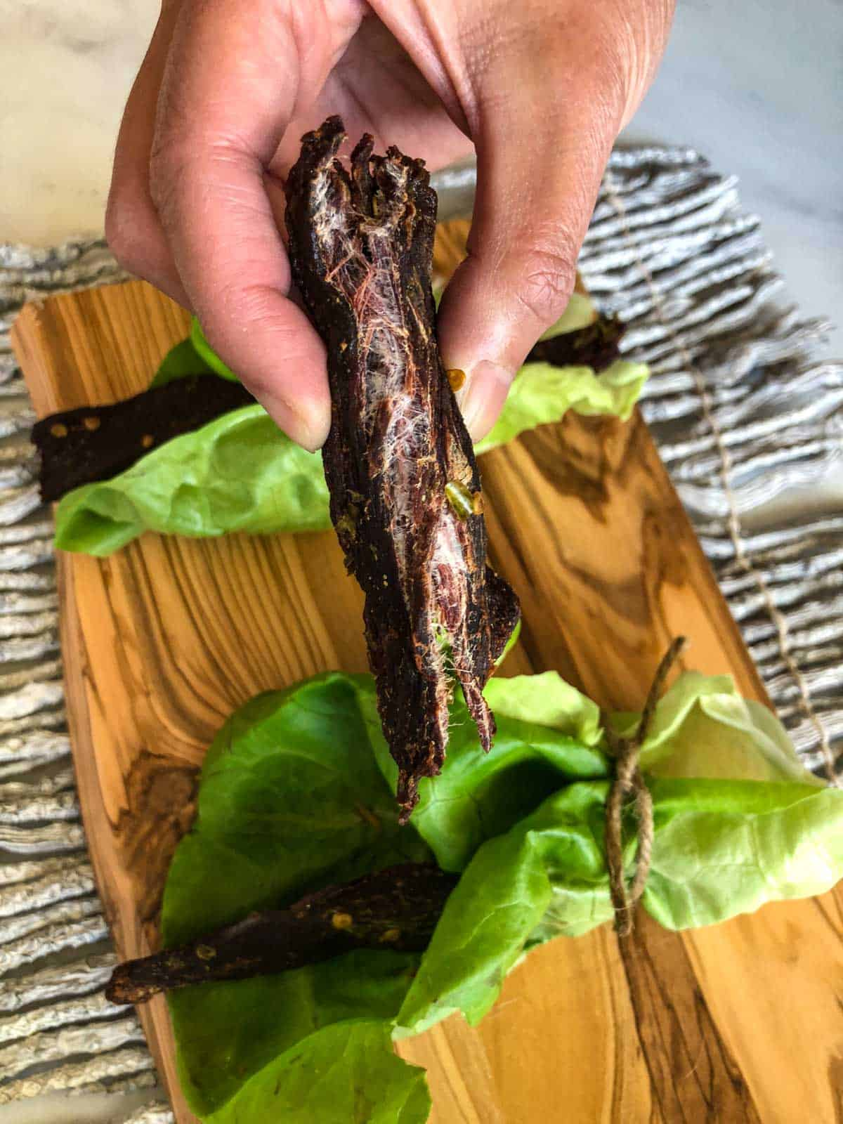 Deer jerky ripped in half showing it's finished with cutting board in background