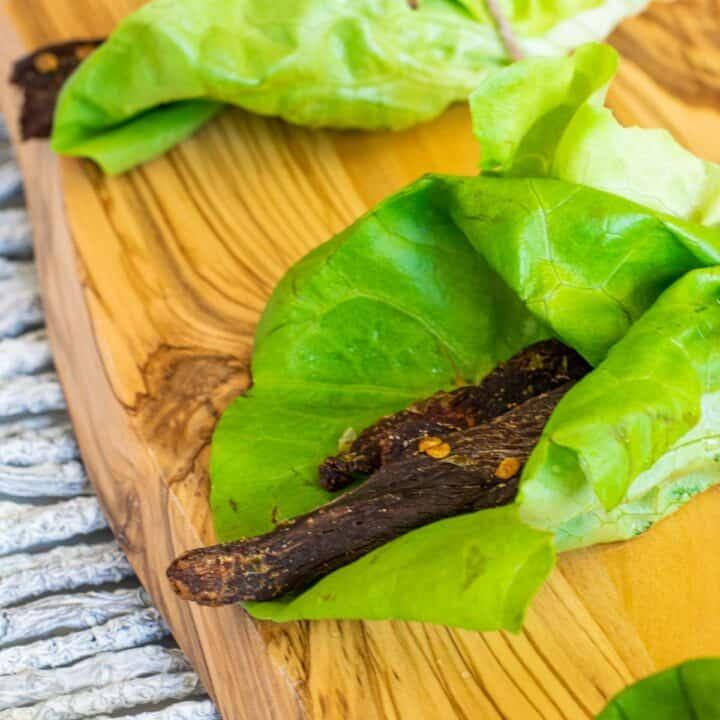 Deer jerky in lettuce wrap on cutting board