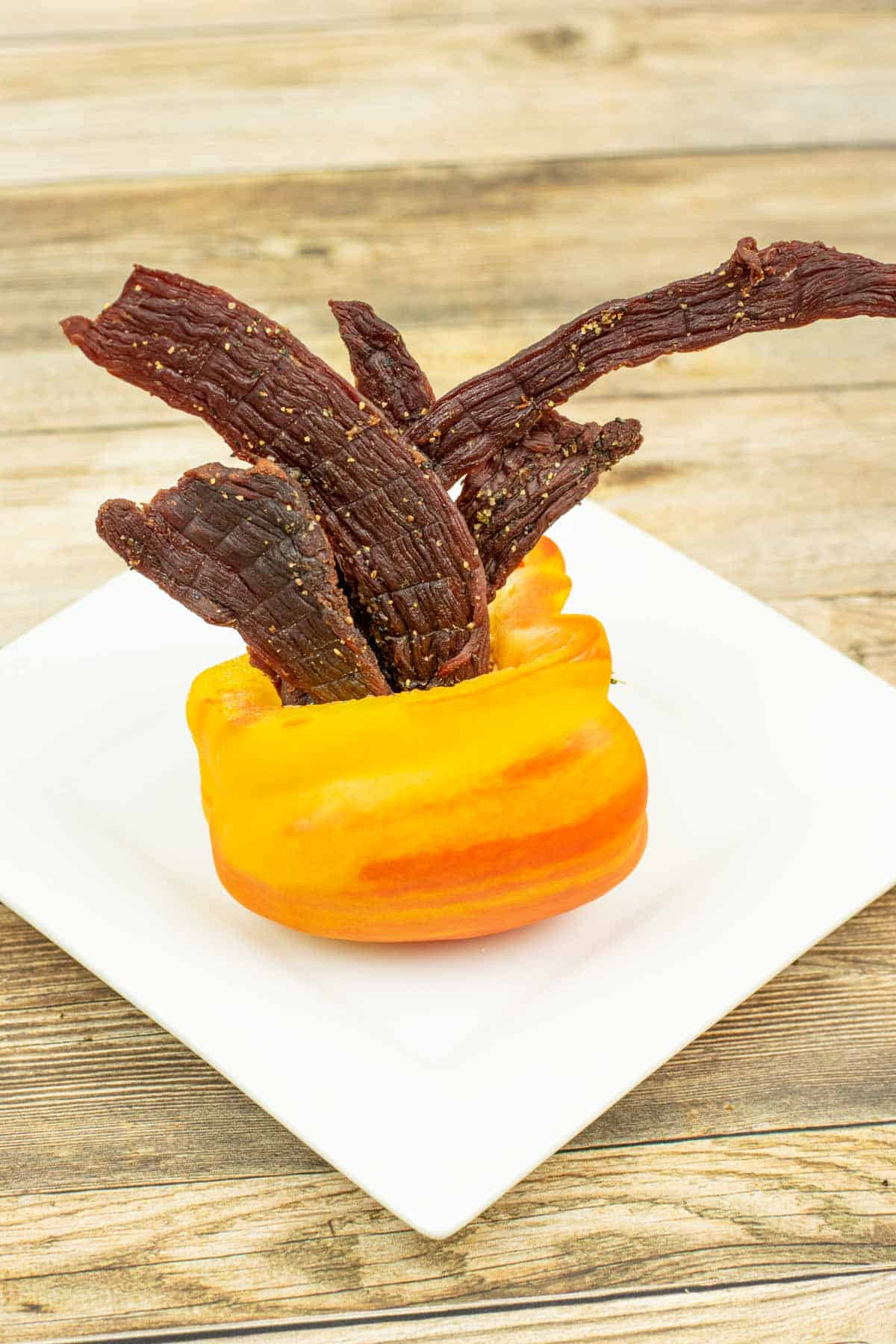 Tangy beef jerky coming out of an orange bell pepper on a white plate