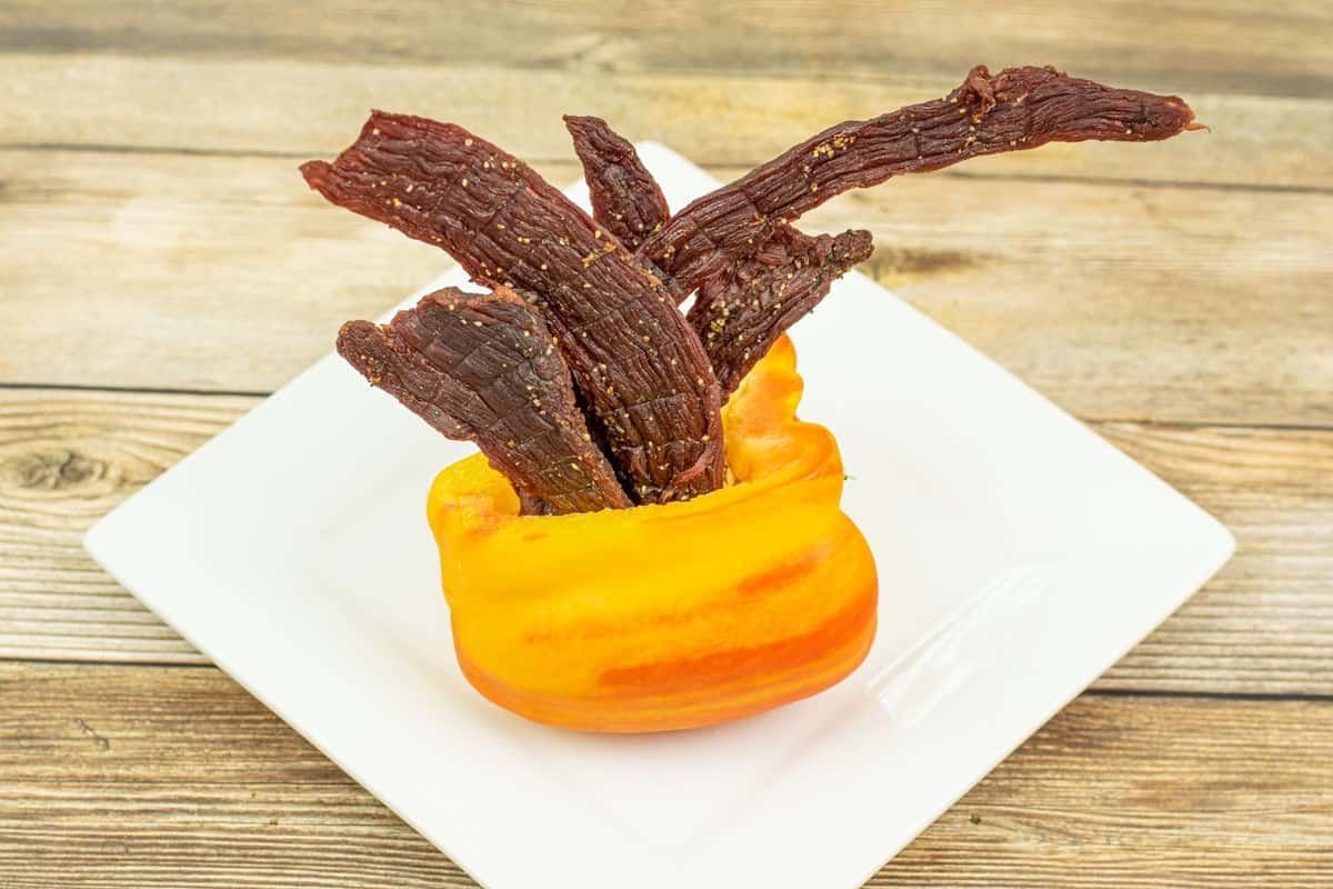 Tangy flavored beef jerky in orange bell pepper on plate