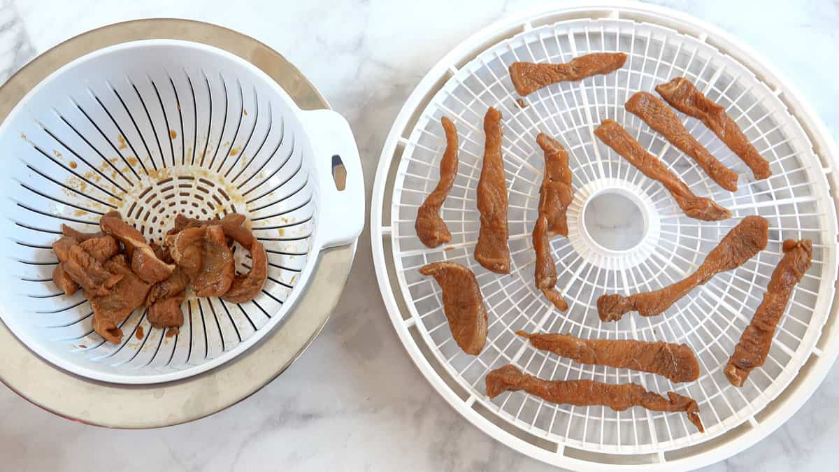 turkey jerky in colander and on dehydrator tray