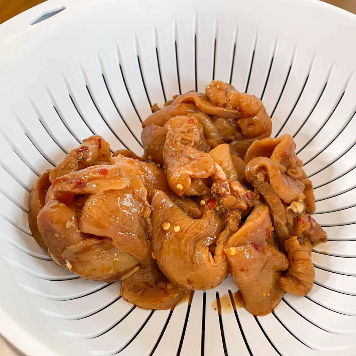 marinated chicken strips straining in colander