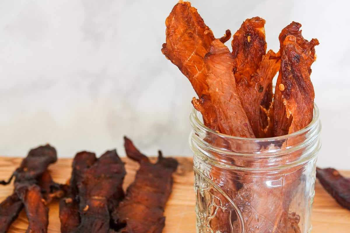 Chicken jerky in mason jar on cutting board with marble background